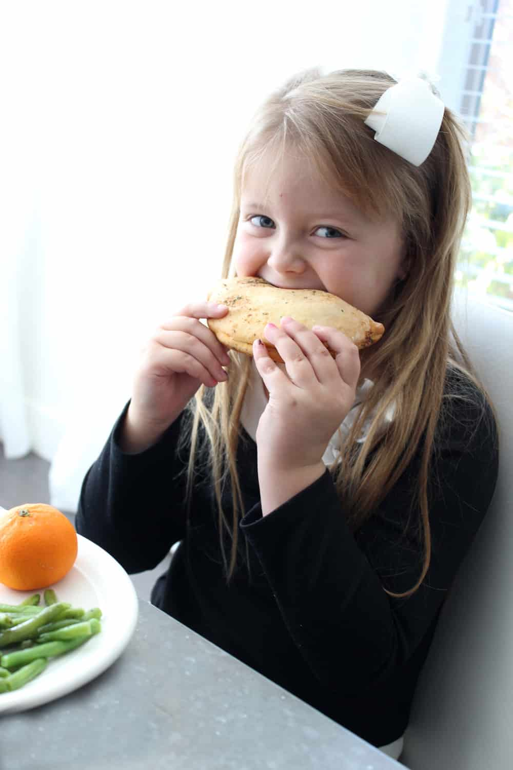 Little girl eating a calzone.