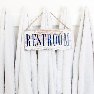 Cute diy restroom sign hanging on some towels.