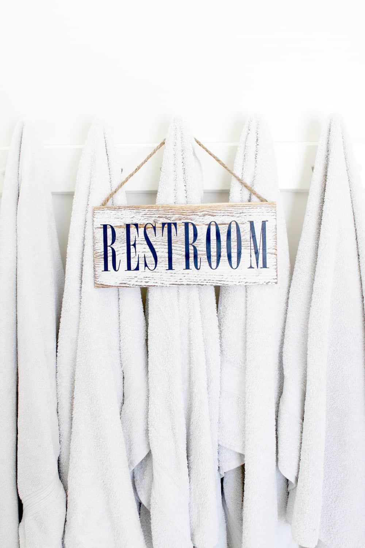 Cute diy restroom sign hanging on some towels.