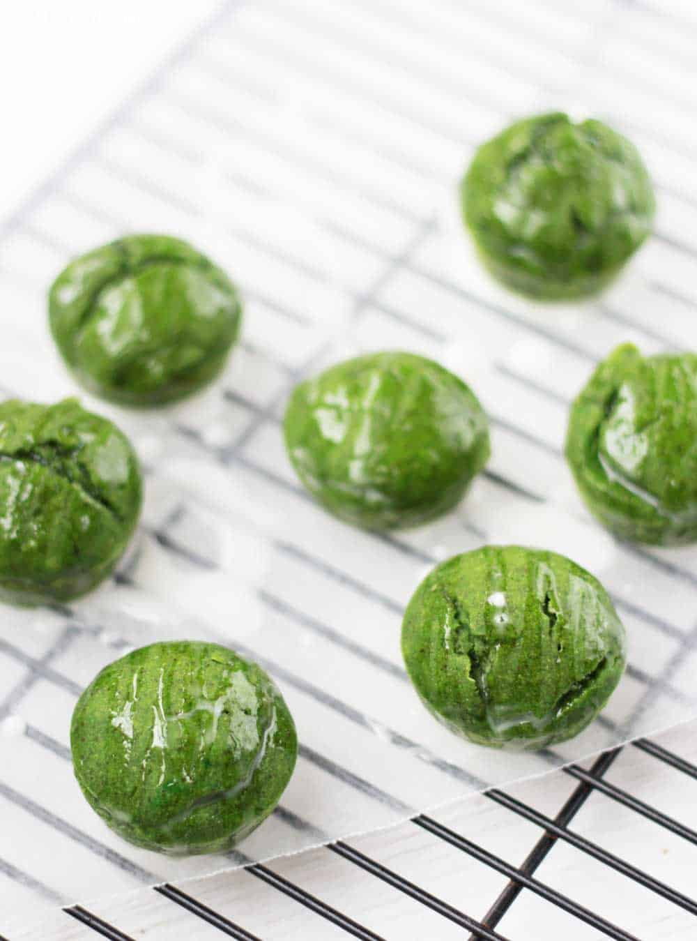 green monster muffins on a cooling rack with icing drizzled over