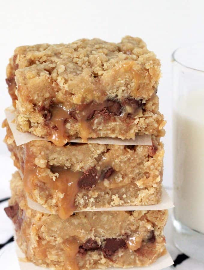 Carmelitas, layered oatmeal chocolate and caramel dessert bars, with a glass of milk on the side.