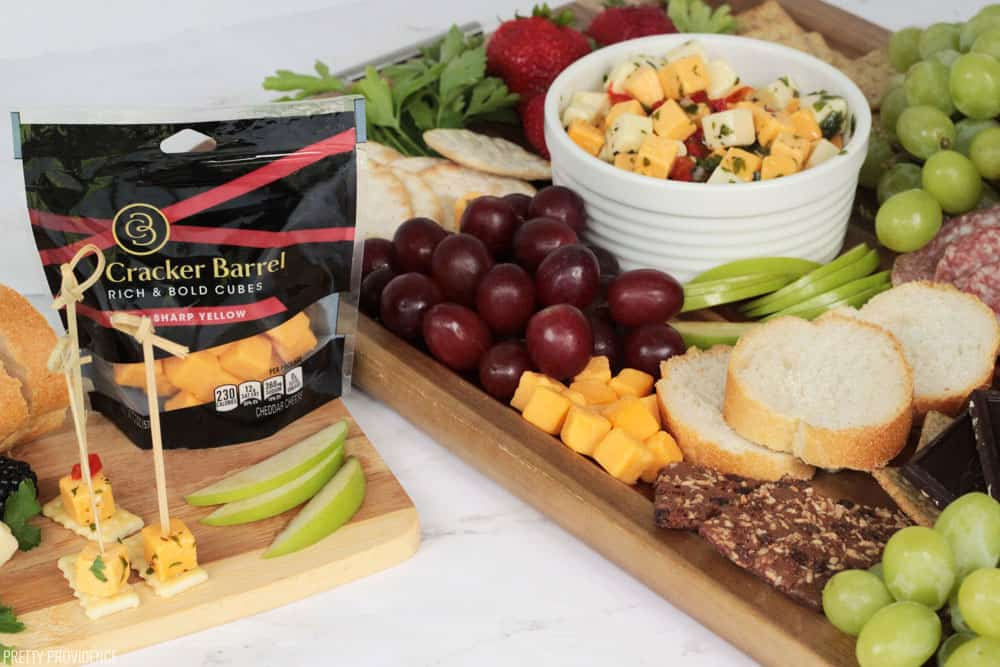 Cheese board with marinated cheese, salami, sharp cheddar, granny smith apples, berries, dark chocolate and baguette.