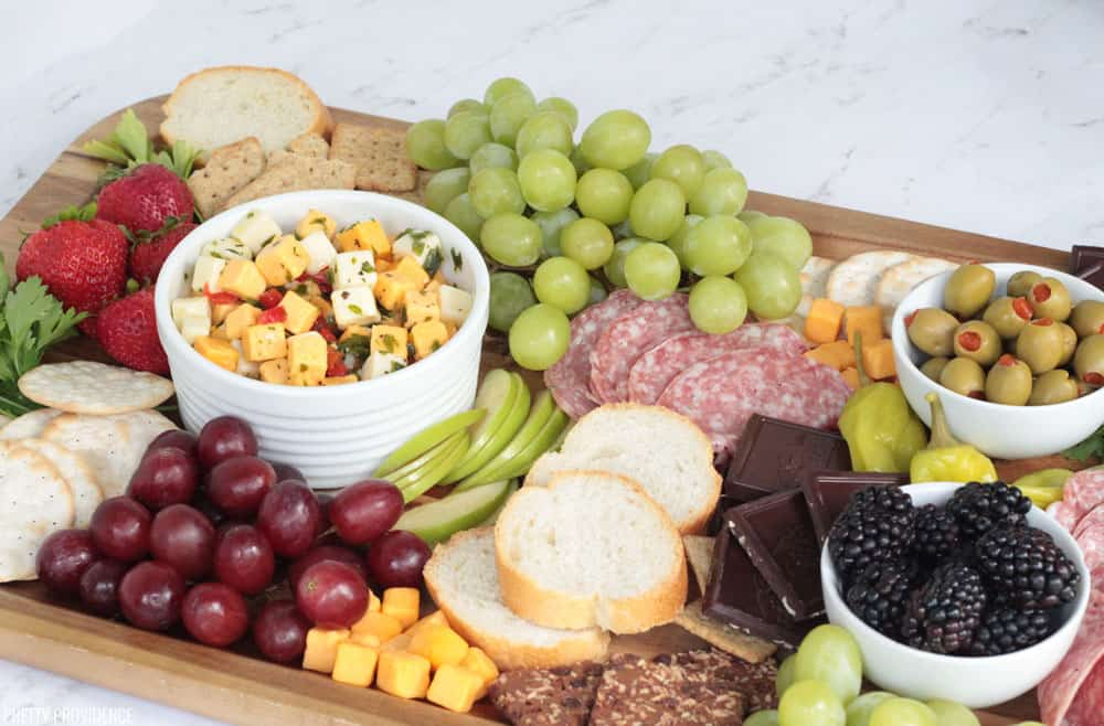 Simple cheese board with fruit, grapes, bread, chocolate, crackers.