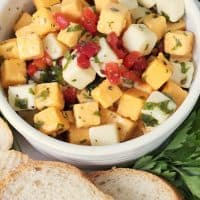 Marinated cheese in a white bowl, with yellow and white cheese cubes, pimentos, parsley, marinade and fresh baguette.
