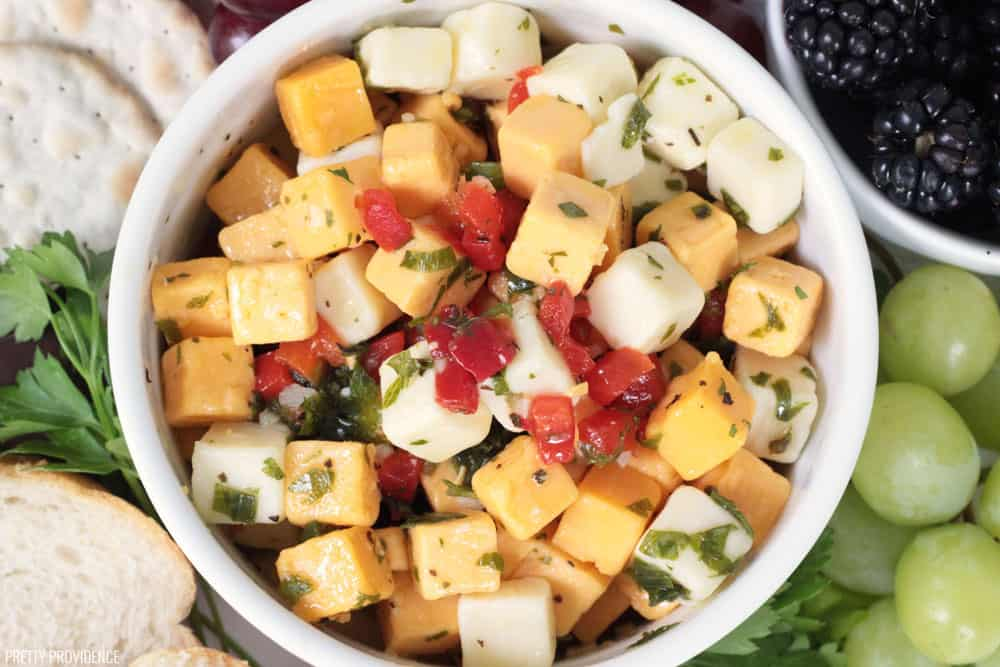 Marinated cheese, yellow and white cheese cubes with parsley and pimentos in a white bowl.