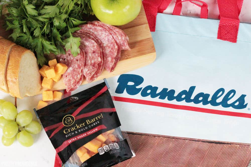 Cheese cube appetizer ingredients, Cracker Barrel cheddar cubes in a bag, with salami, parsley, apples and cheese on a small bamboo cutting board.