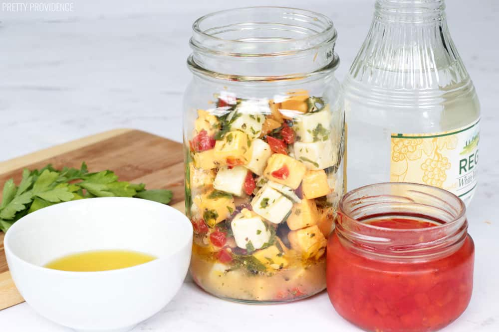 Marinated cheese in a glass mason jar, olive oil, pimentos and white wine vinegar, and parsley. Make ahead and serve room temperature.