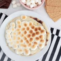 S'mores dessert quesadilla on a white plate with toasted marshmallows on top, surrounded by graham crackers, hershey bar and graham crackers.