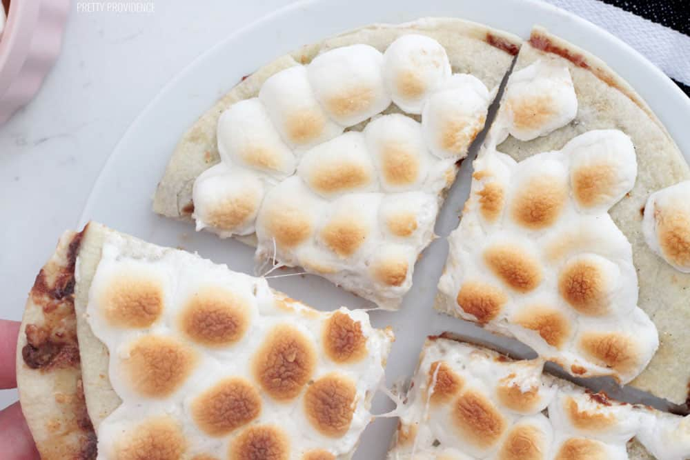 Dessert Quesadilla covered in toasted marshmallows on a white plate, cut into four triangles..