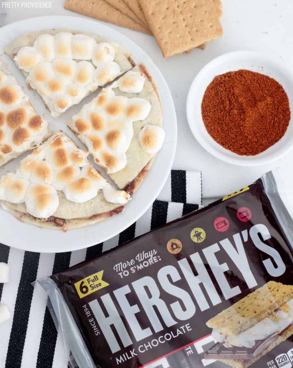 S'mores Quesadilla with toasted marshmallows on a white plate, over a striped towel, with Hershey's bars, cayenne pepper and graham crackers surrounding it.