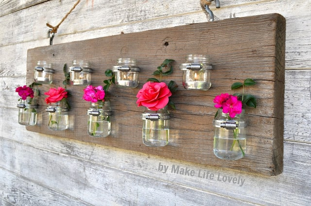 Wood plank hanging with repurposed baby food jars attached being used as flower vases and candle holders, on an outdoor wall.