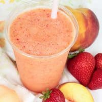 Caribbean Passion smoothie with peach slices, strawberries and a pink straw as garnish.