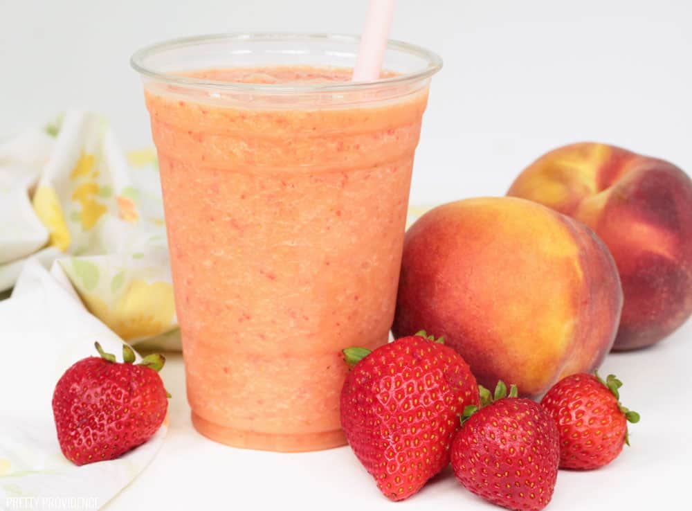 Jamba Juice Caribbean Passion Smoothie with strawberries, peaches and a pink straw.