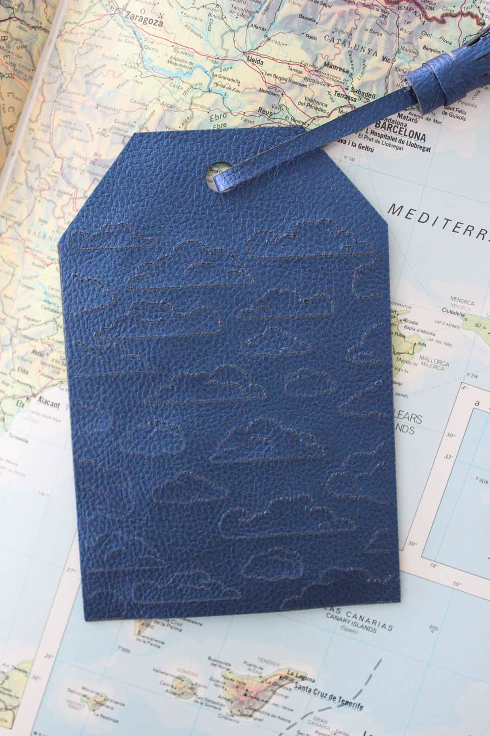 finished blue luggage tag with clouds engraved on it