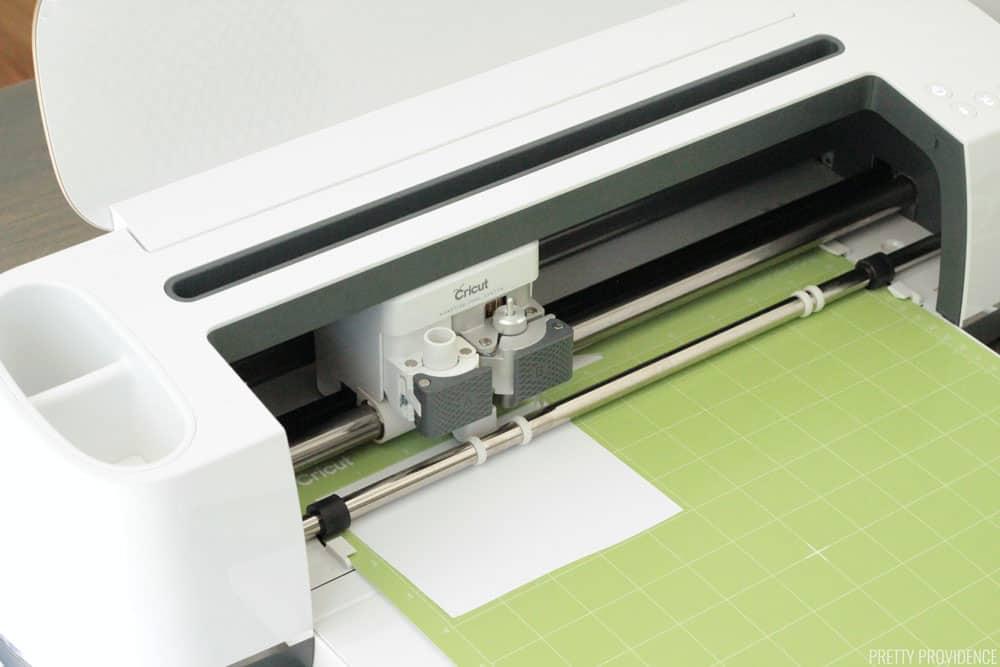 Cricut Maker machine with a green Standard Grip mat in it, cutting a small sheet of iron-on vinyl.