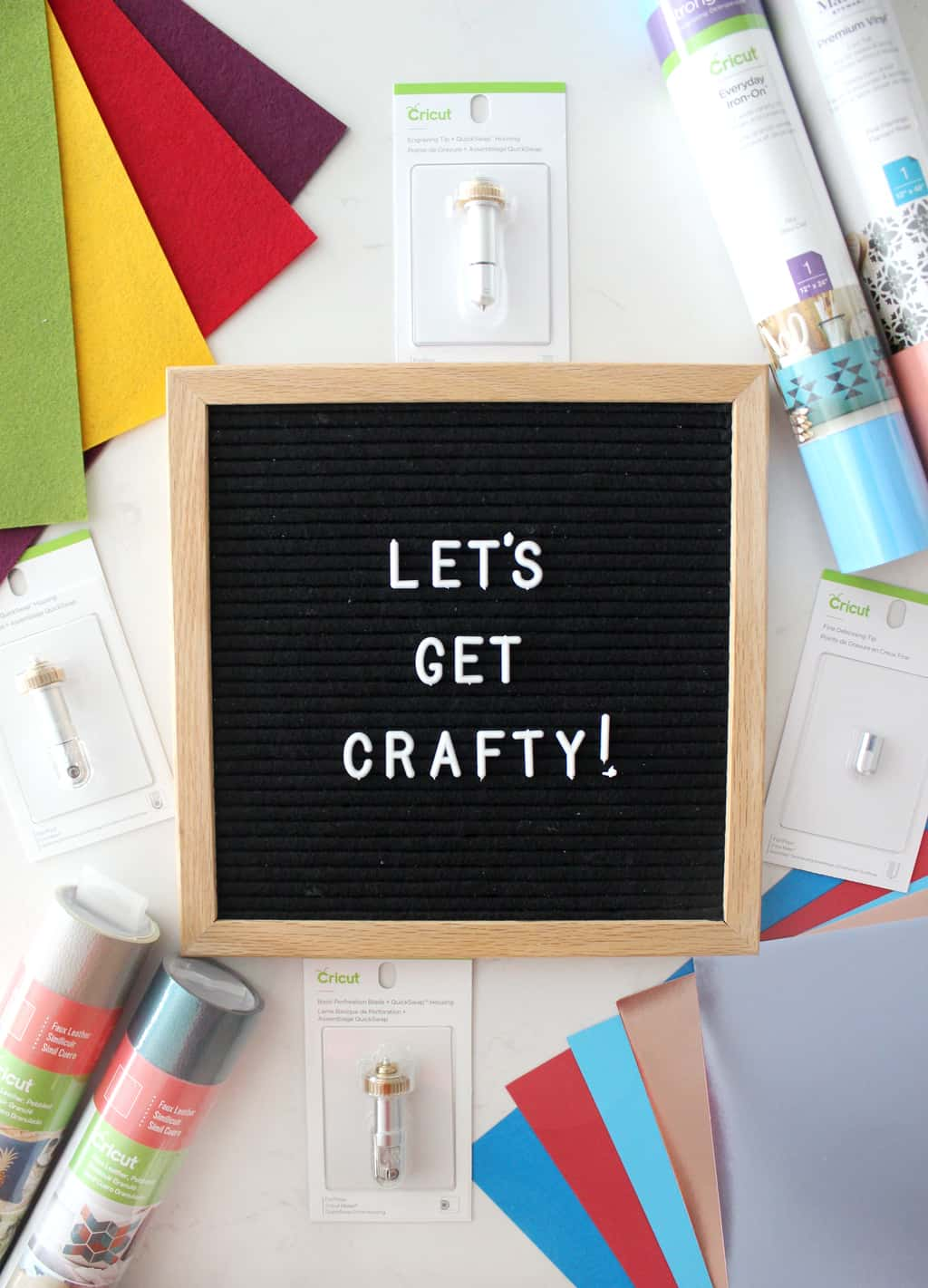 "an assortment of craft supplies surrounding a letter board that says ""let's get crafty"""