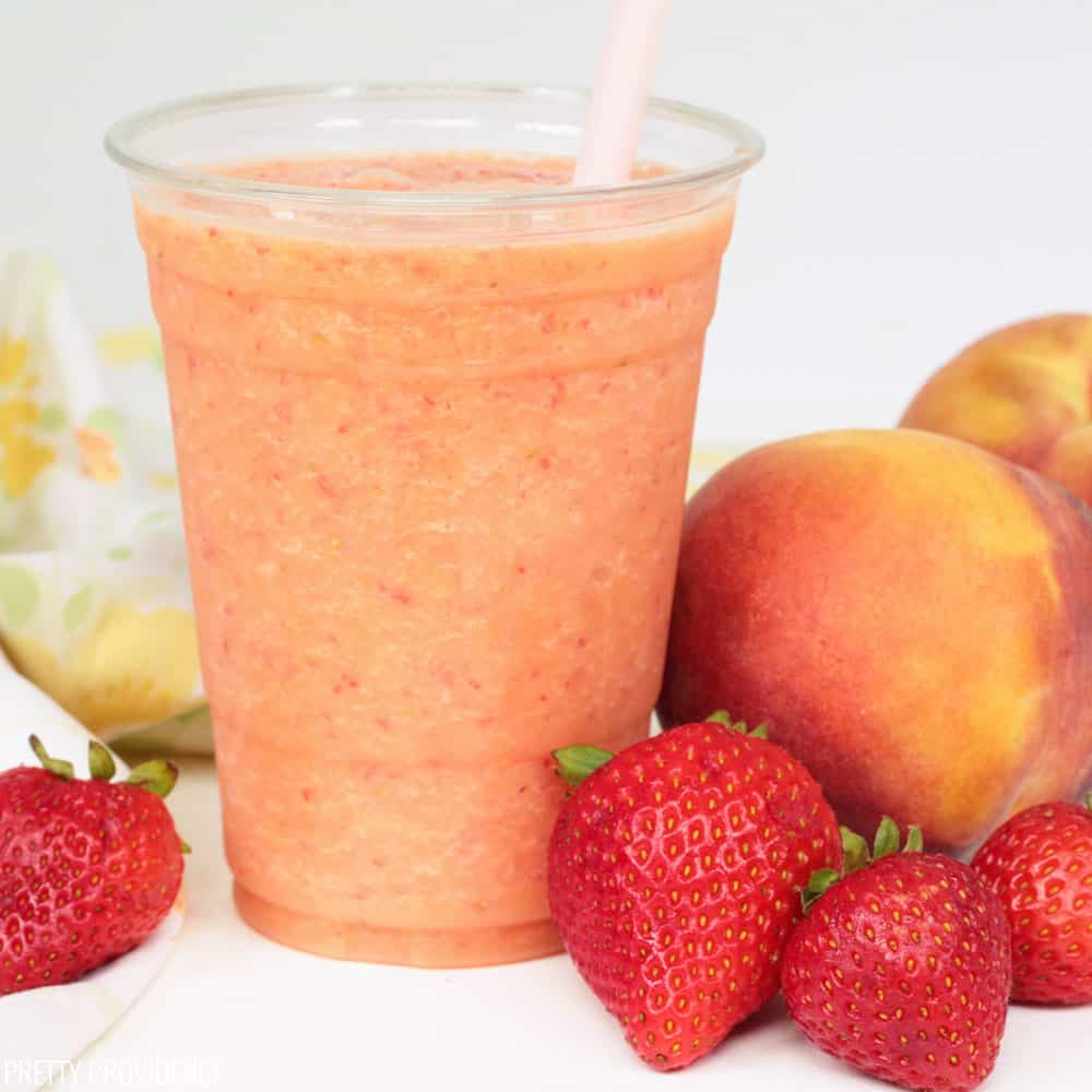 Caribbean passion smoothie with strawberries and peaches on the side.