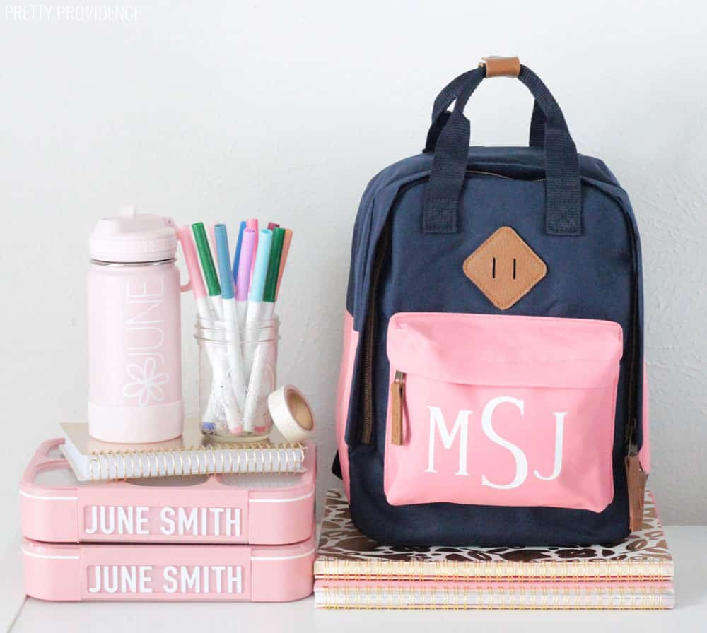 Personalized Kids Backpack, water bottle, and lunch boxes on top of notebooks. Jar of markers and washi tape.