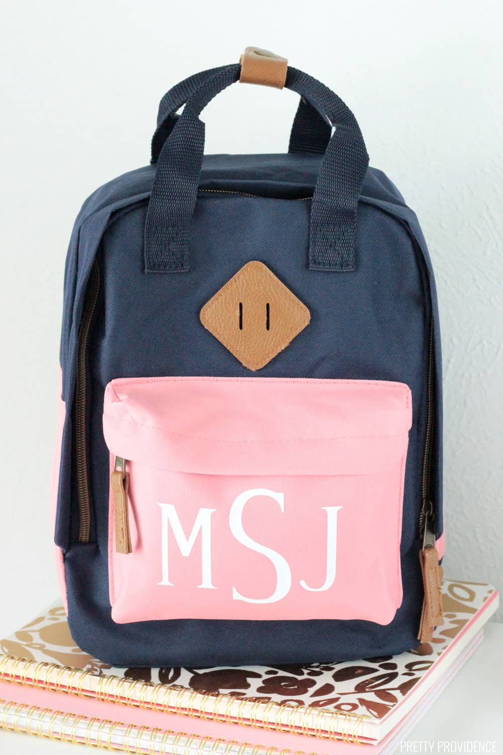 Navy blue backpack with a pink pocket monogrammed with letters M S J sitting atop two notebooks.