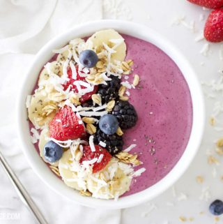 fresh berry smoothie bowl on a white counter with fresh fruit