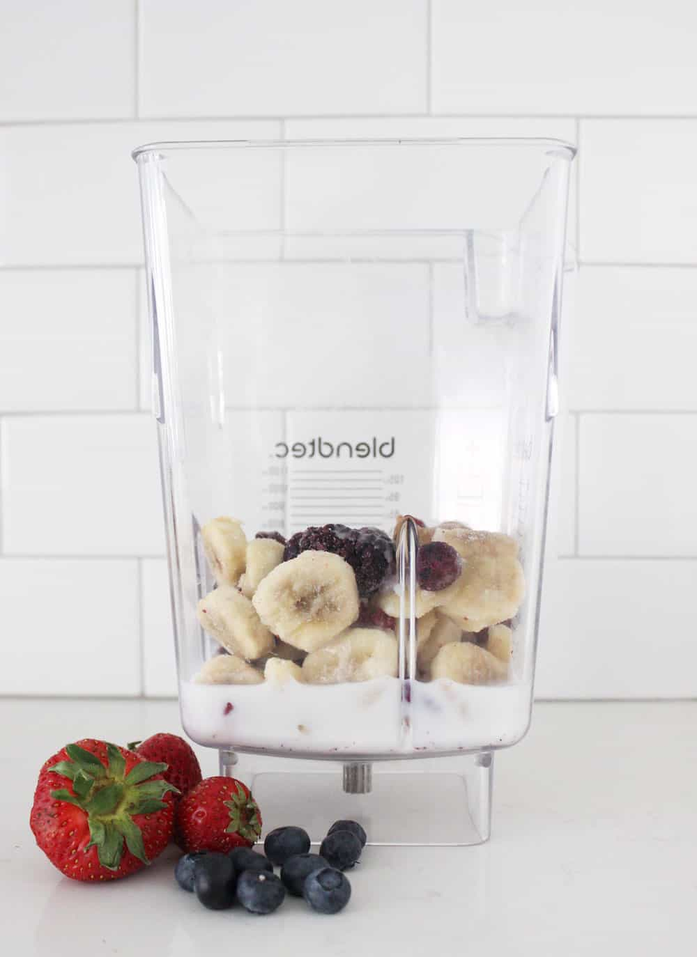 smoothie ingredients in a blender on a white counter