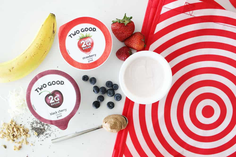 yogurt and fresh fruit on a white counter next to a target bag