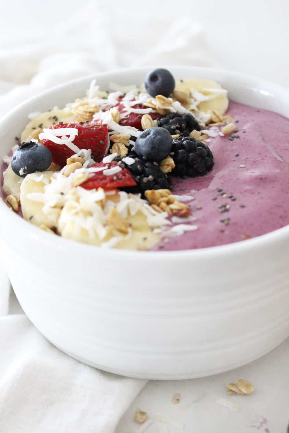 fresh berry smoothie bowl recipe in a white bowl topped with fresh fruit