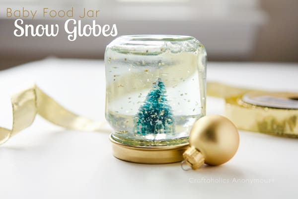 Snow globe from a baby food jar with a gold ornament next to it.