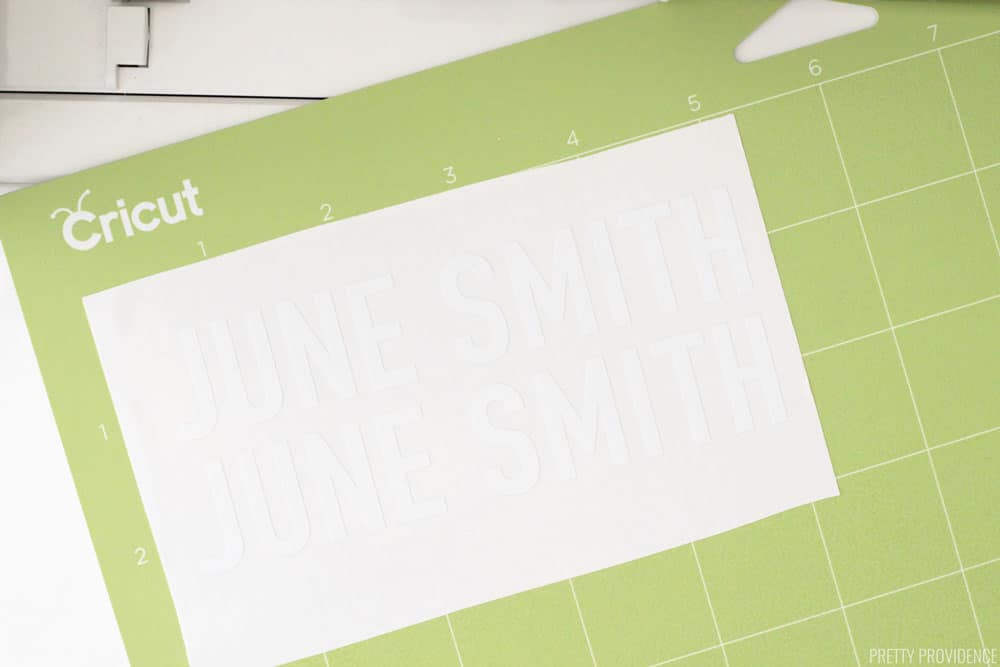 Cricut green StandardGrip cutting mat with a white rectangle of vinyl on it, two labels reading 'June Smith.'