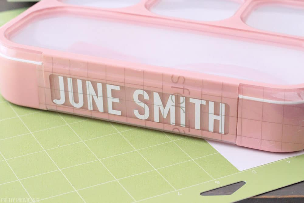Pink bento lunch box with a white label that reads 'June Smith' and Cricut transfer tape over it, all sitting on a green StandardGrip Mat.