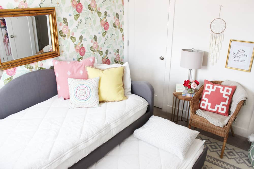 grey trundle with white bedding, a wicker chair and floral wallpaper