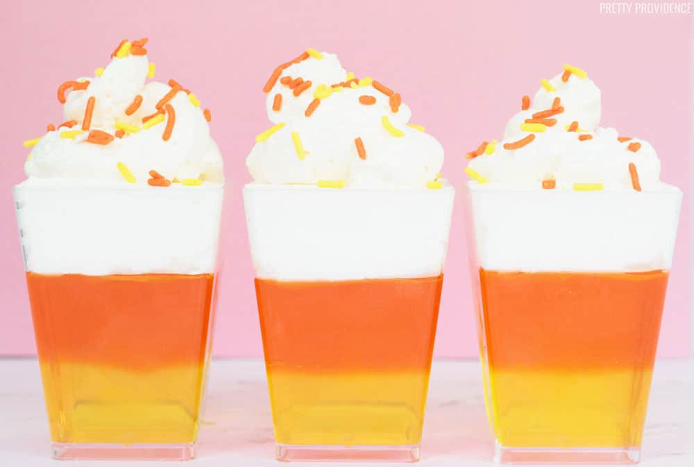Three candy corn jello cups in a row. Yellow jello, orange jello and cool whip topped with sprinkles.