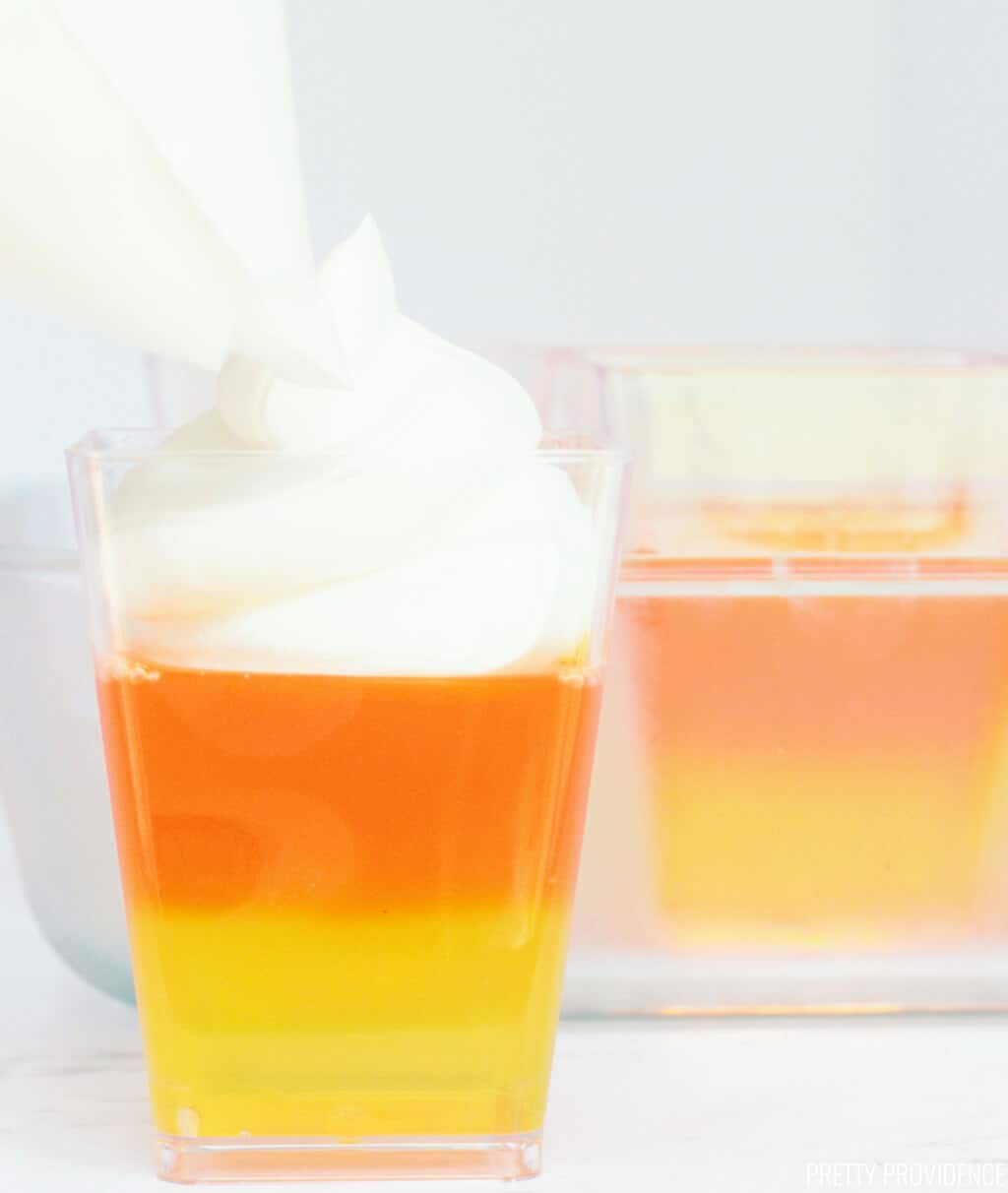 Candy corn Jello with yellow layer, orange layer on top of that and then cool whip being piped onto the top.