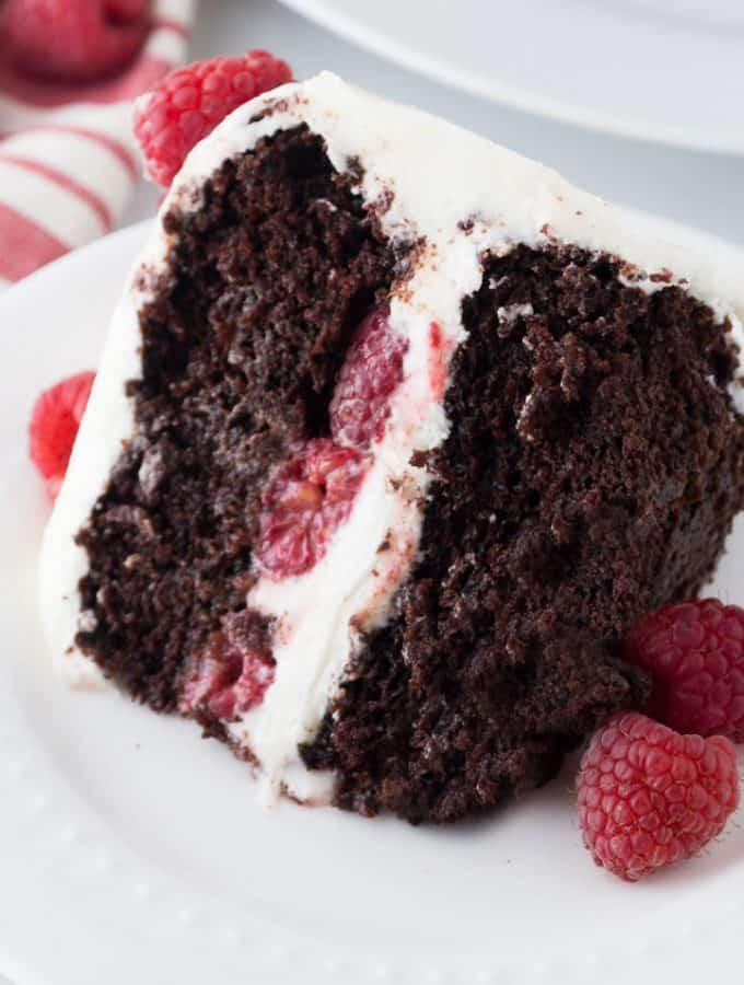 Chocolate Raspberry Cake with cream cheese frosting and raspberries inside the middle layer and on the top, as garnish on a white plate.