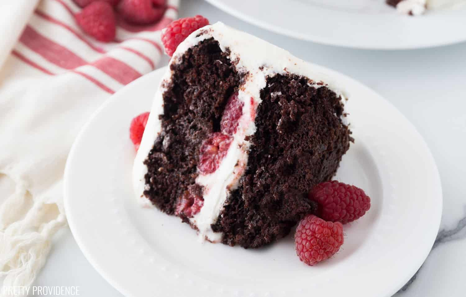 Chocolate Raspberry Cake with cream cheese frosting and raspberries inside the middle layer and on the top.