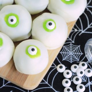 Eyeball cake balls - white cake balls with lime green frosting and candy eyeballs on a bamboo serving board and black spiderweb tea towel.