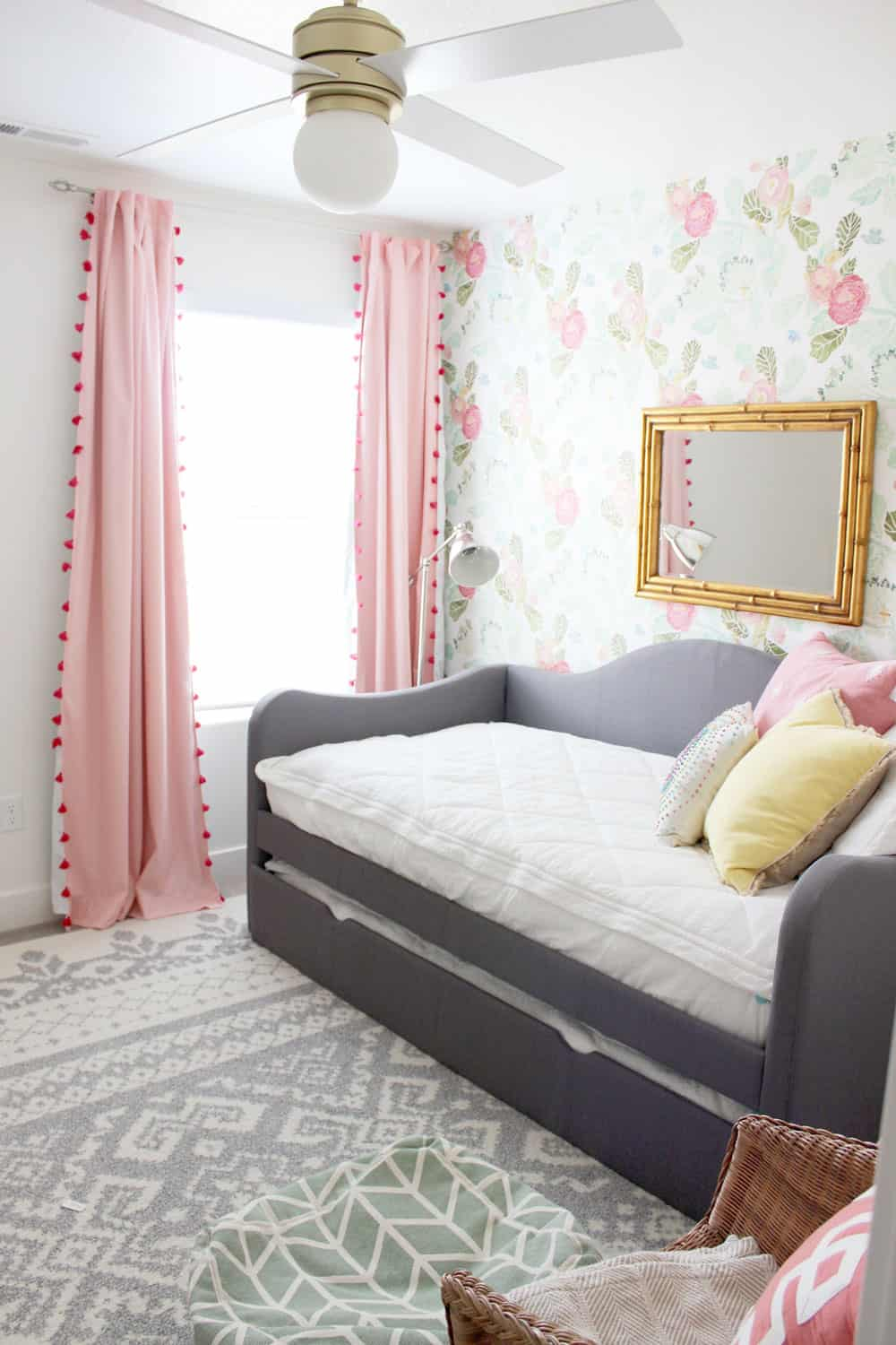 grey trundle bed on moroccan rug with pink pillow fort blackout curtains