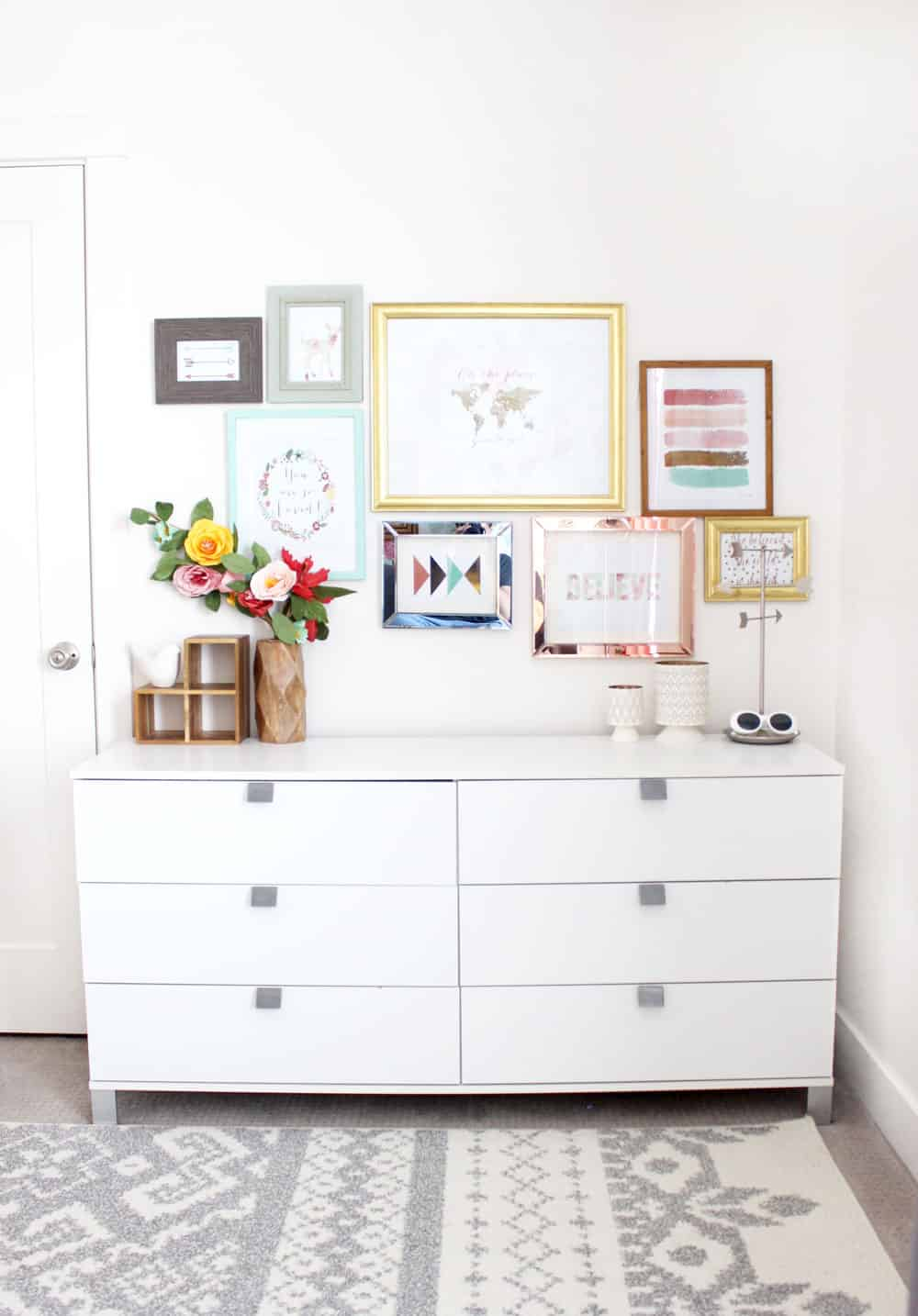 a modern white dresser underneath a colorful gallery wall