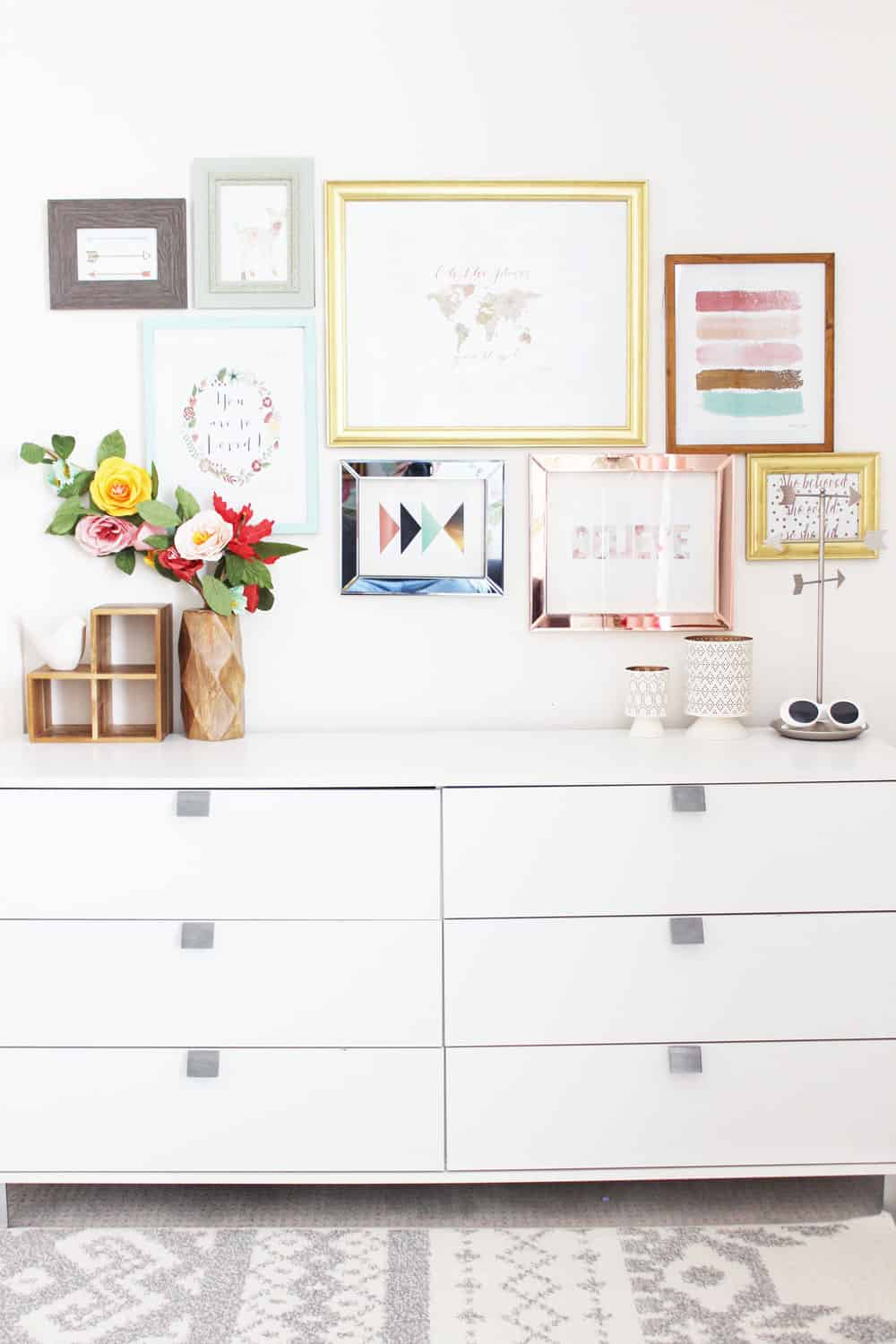 white dresser with a colorful gallery wall laid out above it.