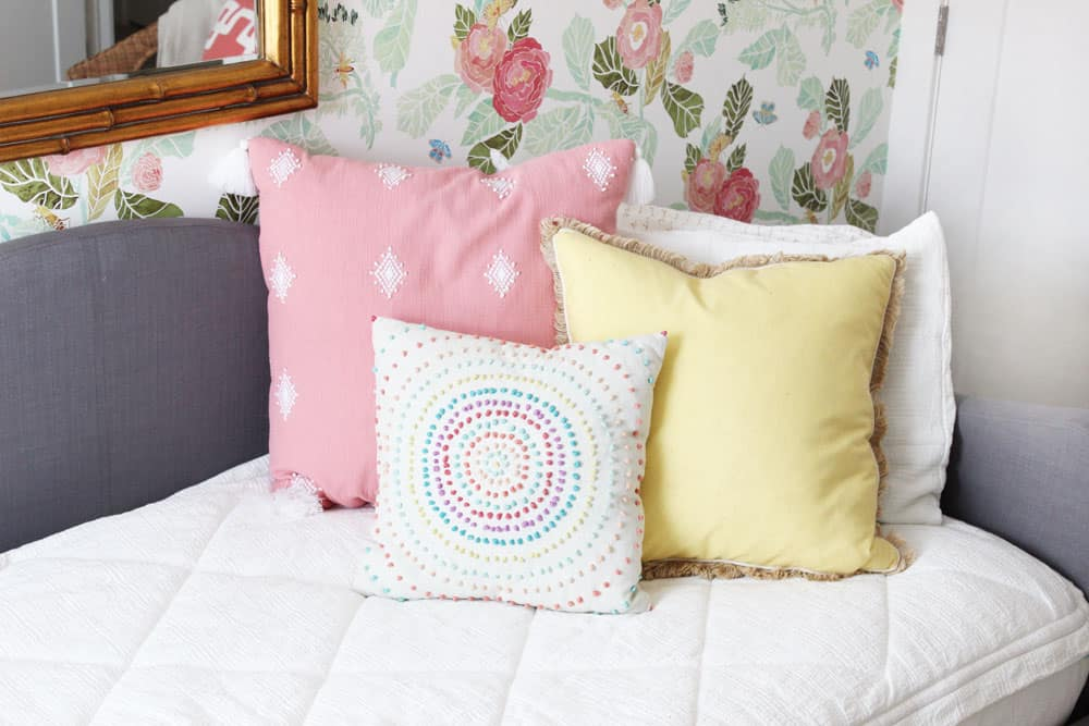 fun pink and yellow pillows on white zipper bedding against a floral wall