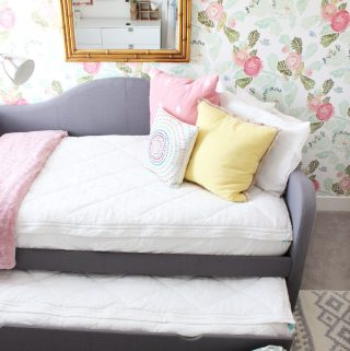 a grey trundle bed with the trundle pulled open halfway