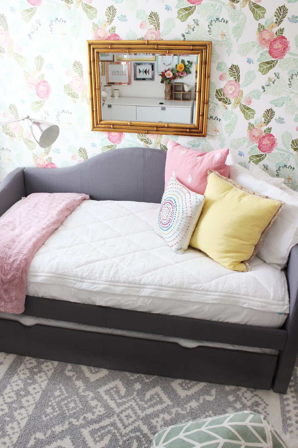 girls room with bed against a floral wall and grey tribal rug