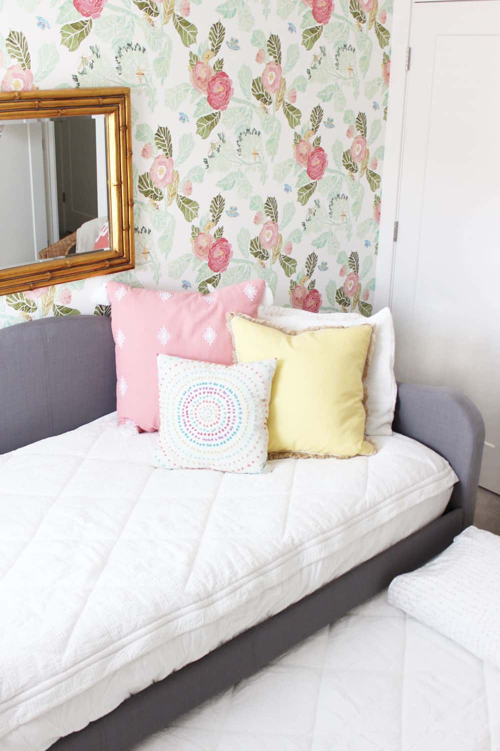 girls trundle bed open with white bedding and colorful pillows