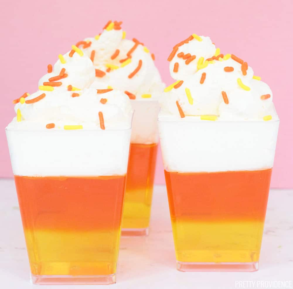 Three candy corn Jello cups, with three layers: yellow, orange, and white with sprinkles on top.