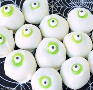 Halloween Cake Balls that look like Eyeballs. Green cake dipped in white candy, green icing and candy eyeballs.