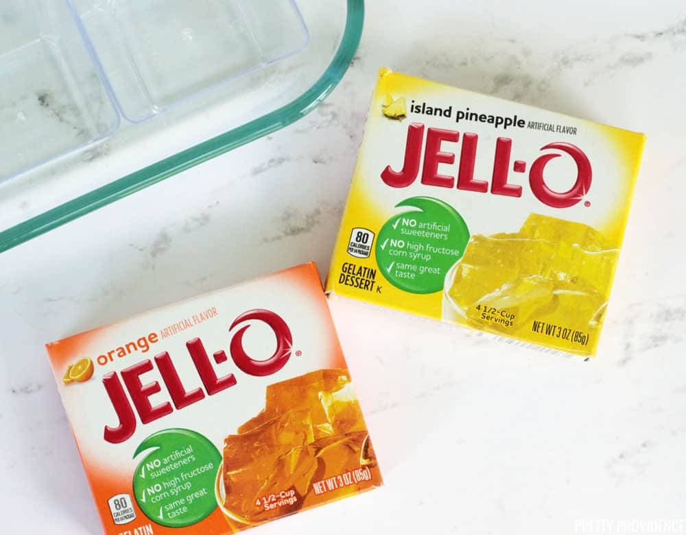 Orange Jello and Pineapple Jello boxes on a marble board, with clear dessert cups next to them.