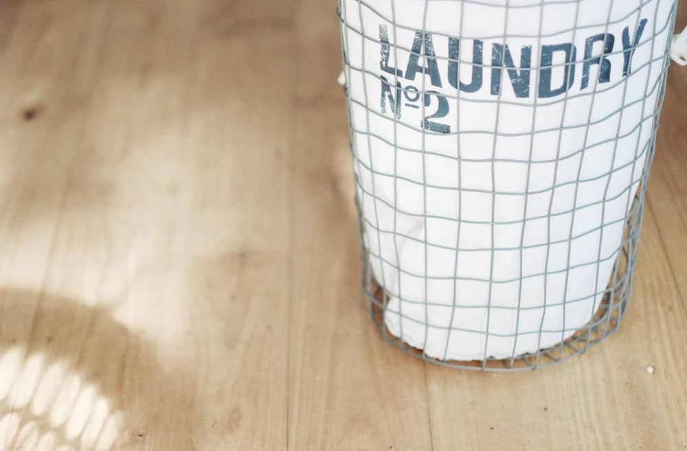 a wire laundry basket on a light wood floor