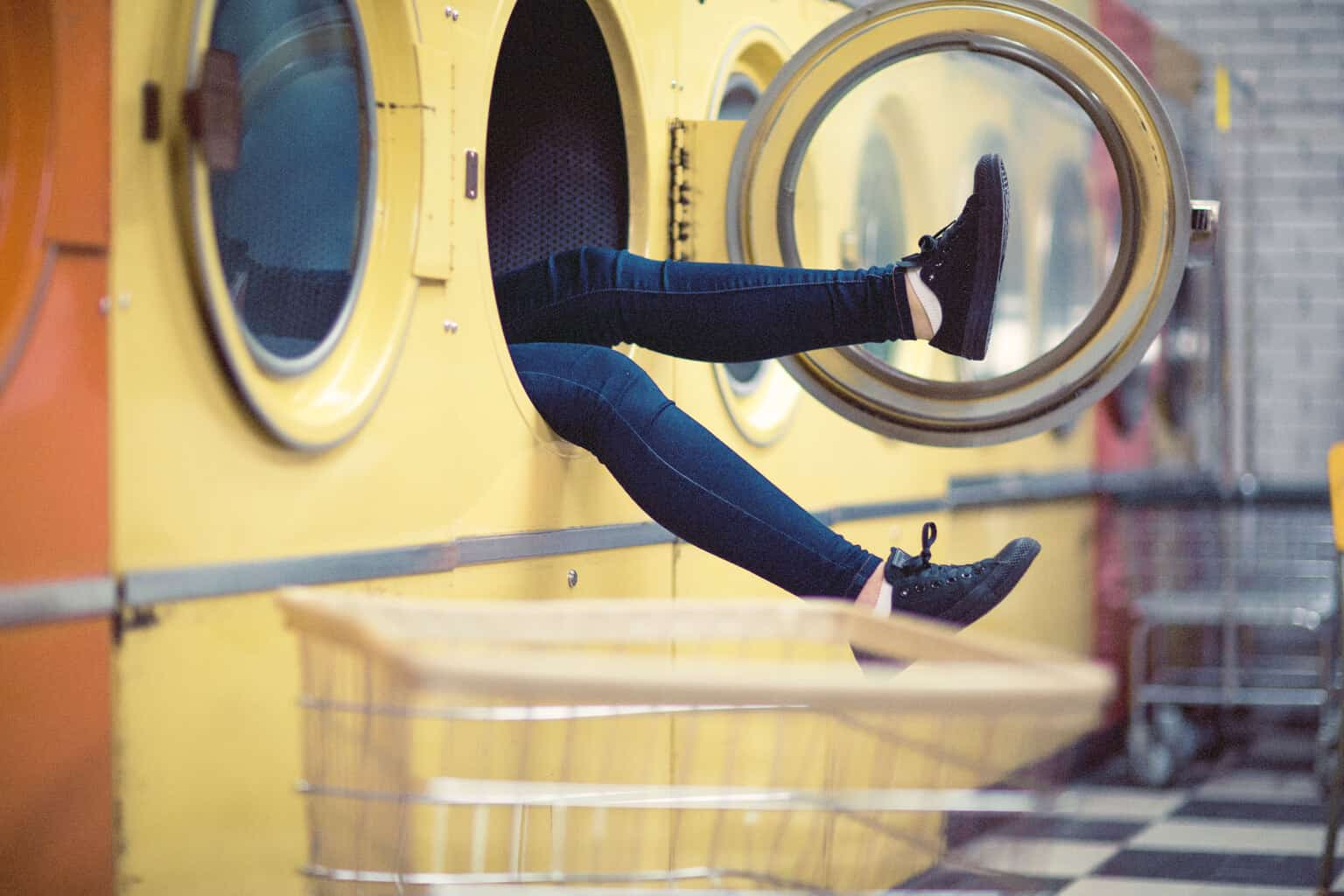 a girl in dark jeans sticking her legs out of a washing machine