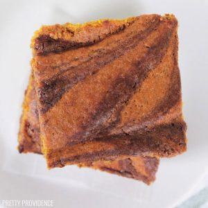 Square Pumpkin Brownies swirled stacked on a white plate.