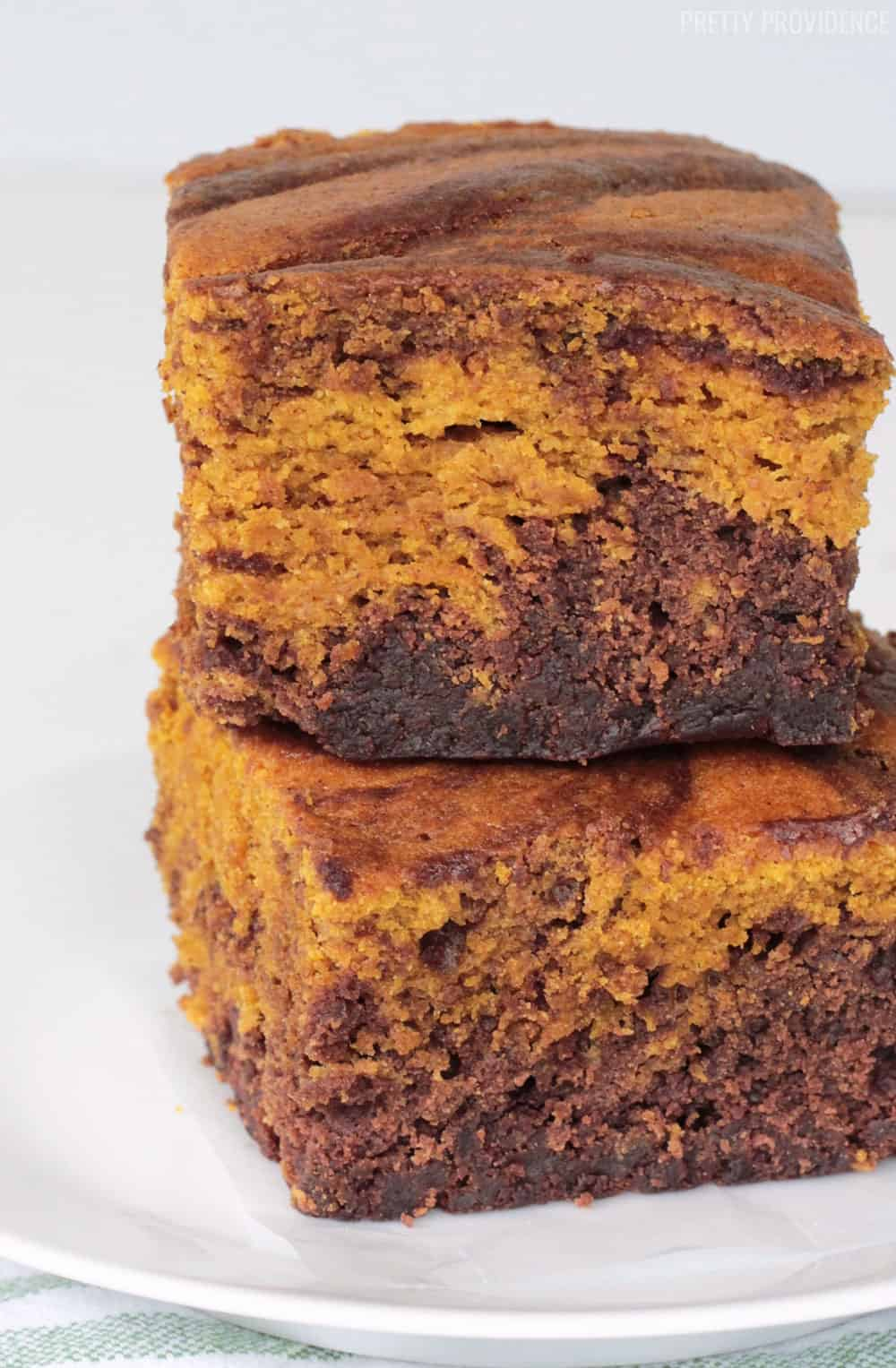Two Pumpkin Brownies swirled brownie and pumpkin cake stacked on top of each other on a white plate.